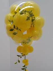 Colourful celebrations with bobo balloon stuffed with yellow balloons and leaves