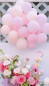 Basket of pink white mix 20 flowers with 10 pastel balloons cluster on top with leaves