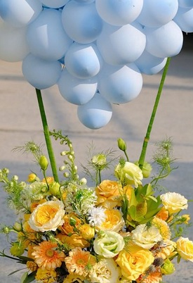 Basket of yellow white flowers with blue balloons cluster on top with leaves