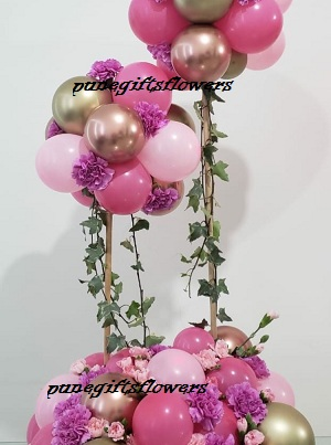 Decorated small and large ballloons 40 balloons shades of pink at bottom and flowers with shades of pink balloons cluster on top of 2 stick